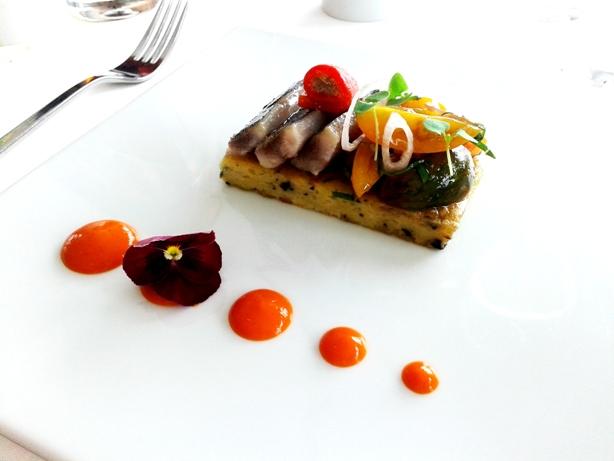 Sardinha assada com uma salada de tomates biológicos e bolo de azeitona